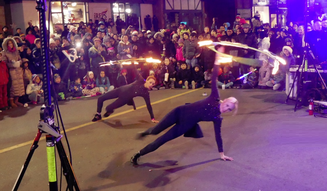fire show with hula hoops entrances audience at outdoor street festival night